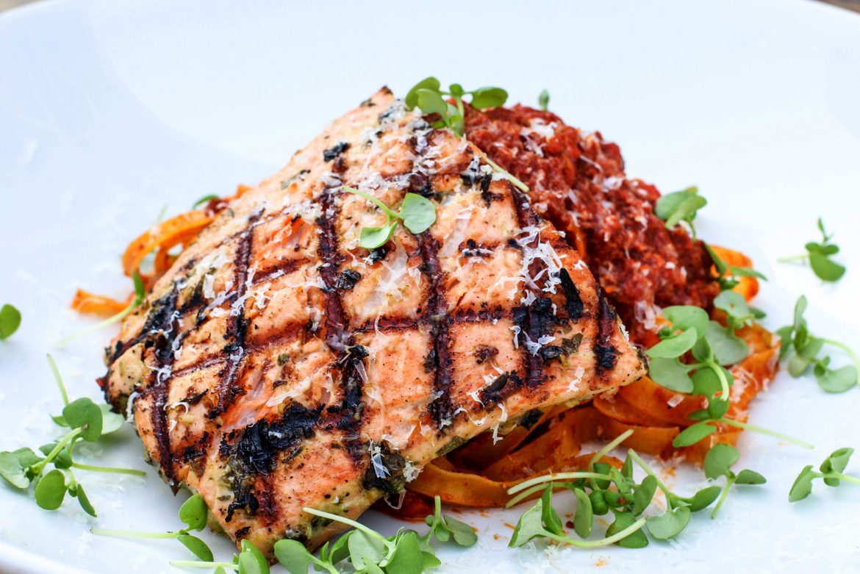 Chimichurri Rubbed Salmon with chorizo bolognese, tagliatelle, micro basil