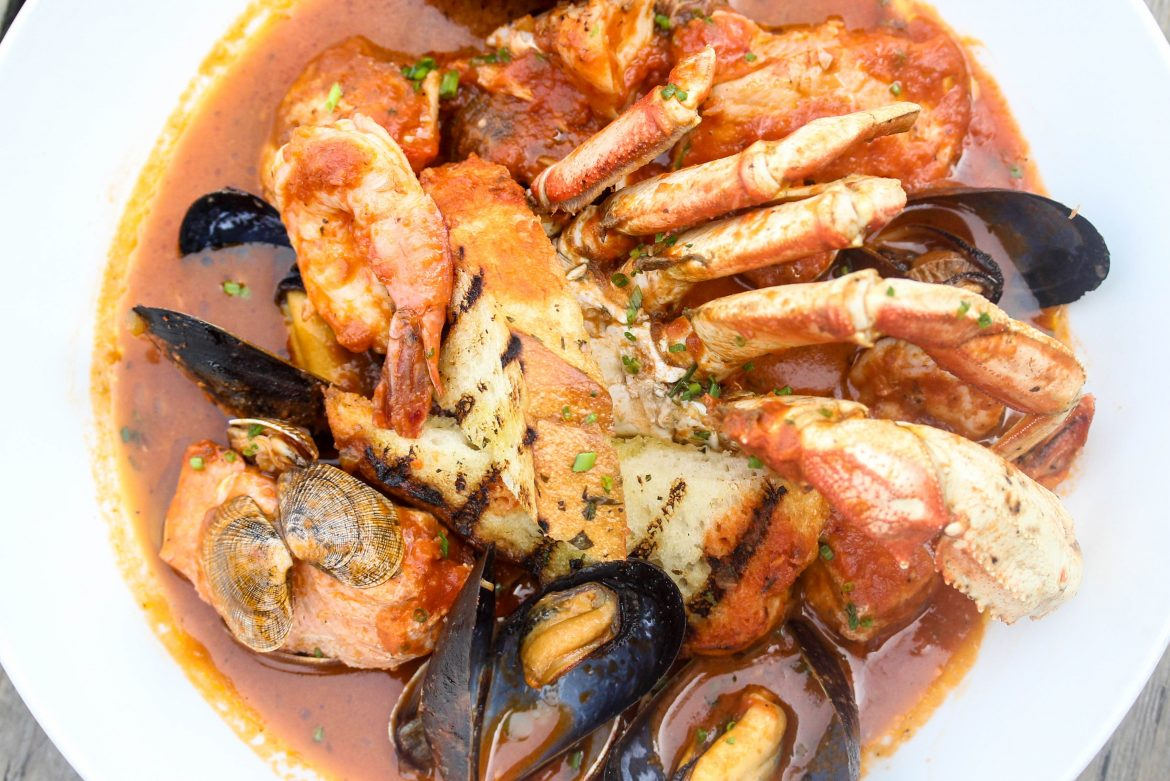 Seafood Cioppino with wild salmon, halibut, manila clams, mussels, prawns, dungeness crab, grilled fremont sourdough